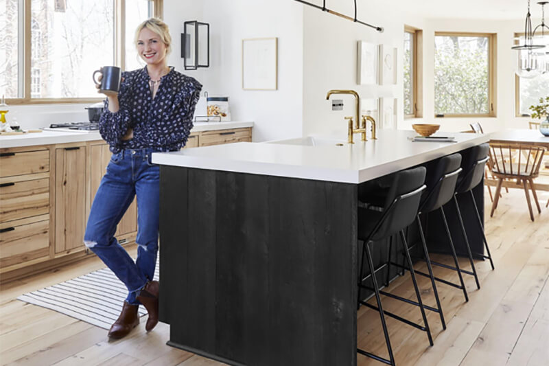 Emily Henderson standing next to large kitchen island in front of Marvin Windows