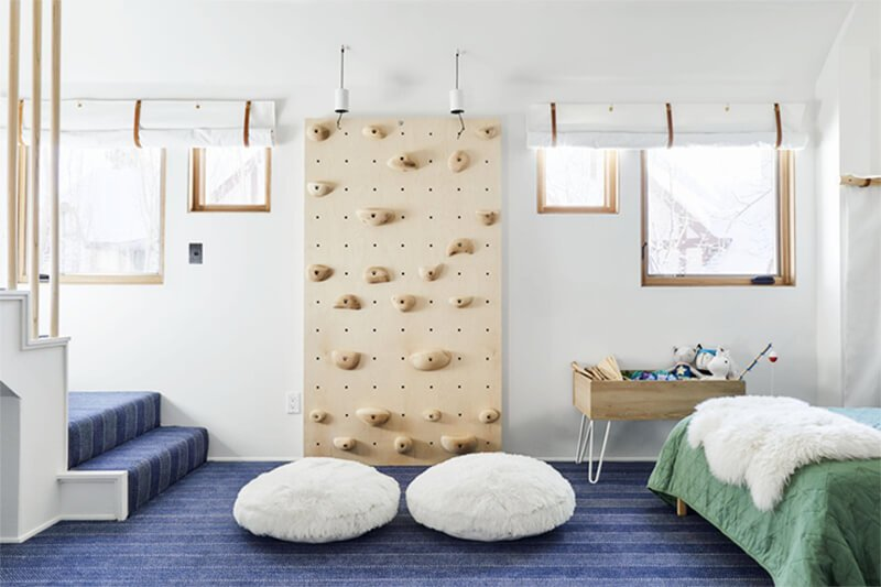 Large bedroom with rock climbing wall and multiple Marvin Windows