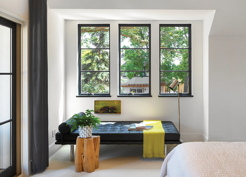 A bedroom with three casement windows.
