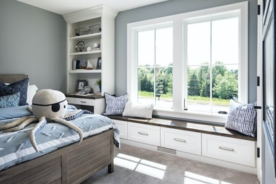A bedroom featuring two casement windows and a window seat.