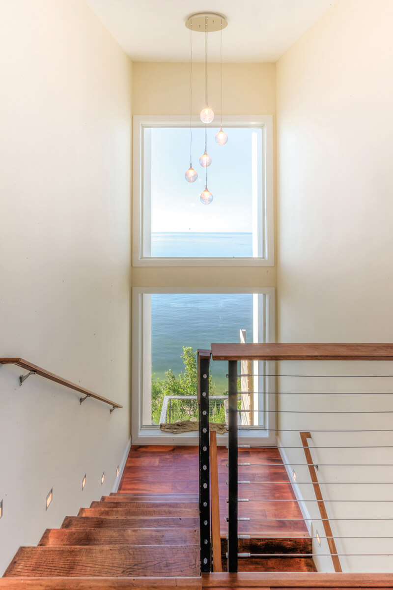 Staircase of beach home with large Marvin Windows