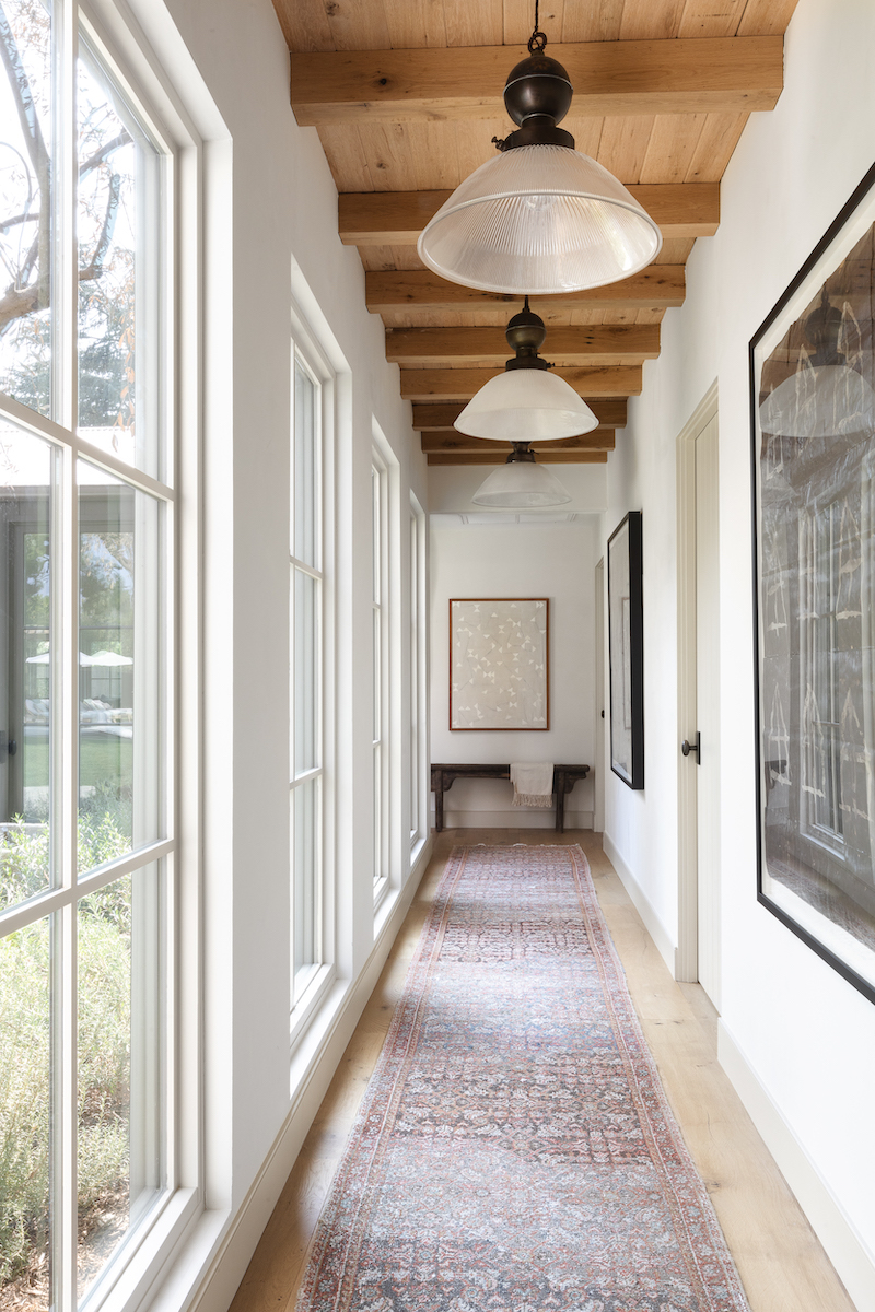 Hallway in Amber Lewis's Belgian farmhouse-style home, featuring floor-to-ceiling Marvin Signature Ultimate windows.