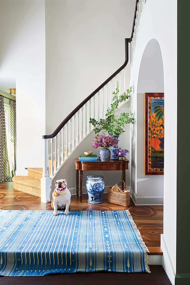 An entryway with a curved staircase with a bulldog sitting on a blue rug.