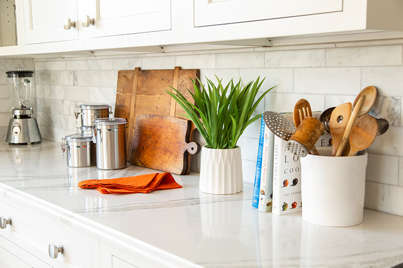 A kitchen counter with a plant, small appliances, cutting boards, and cookbooks.