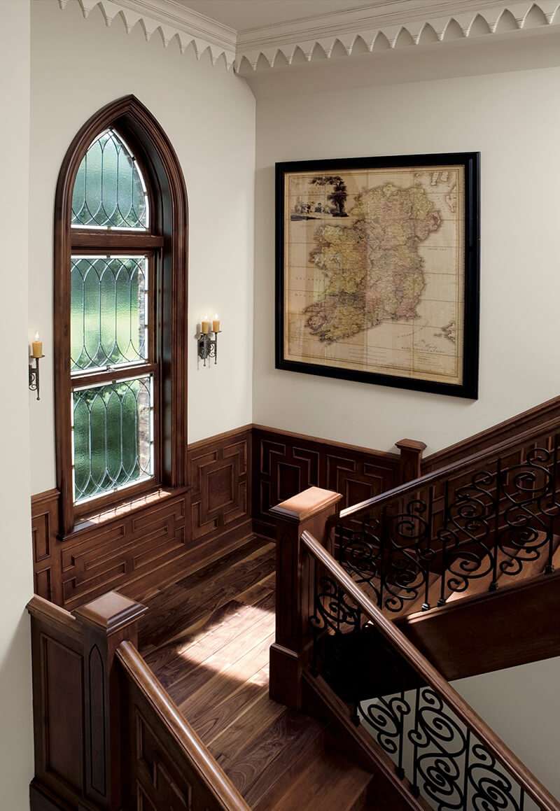 Traditional style staircase looking through historic style Marvin Window