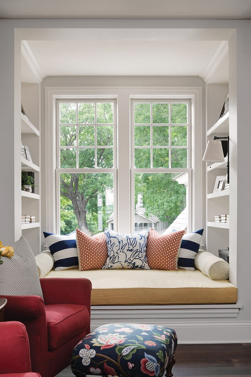 A window seat with built-in shelving and two Marvin double hung windows.
