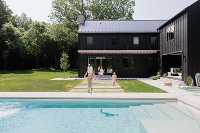 Pool front view of Danish Style Farmhouse home with Marvin windows