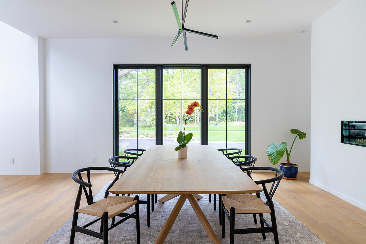 A modern dining room with black Marvin Signature Ultimate windows.