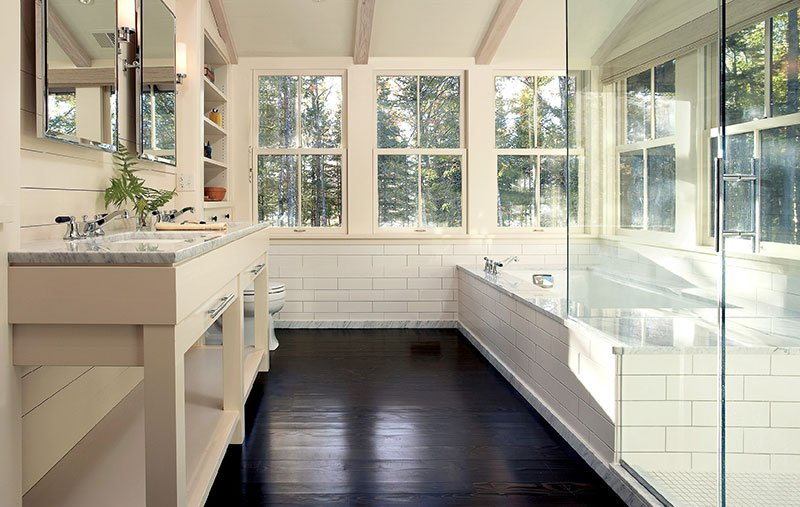 A white bathroom featuring glass shower door, white tile and Marvin double-hung windows.