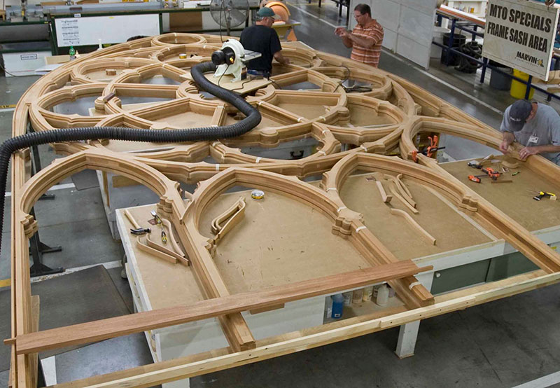 A large, ornate window being made at a Marvin windows and doors factory.