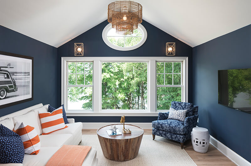 Living room with white double hung windows and navy walls.