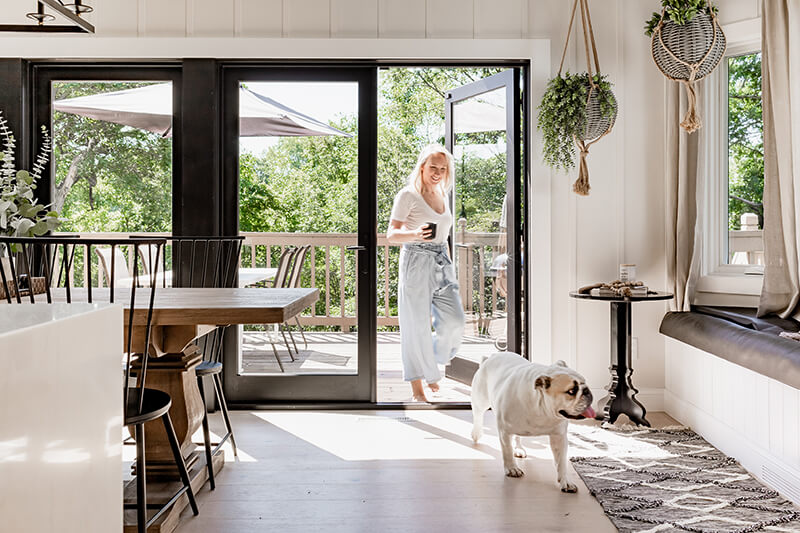 Katie Kurtz and the family bulldog in her redesigned kitchen featuring a Marvin Elevate Swinging French Patio Door.