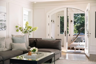 Living room with round top swinging French doors.