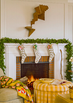 Fireplace with garland and holiday stockings hung on the mantel