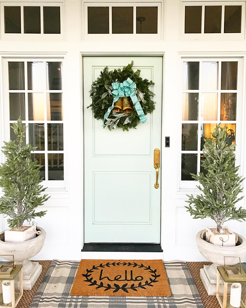 Front door of home with holiday decorations and multiple windows