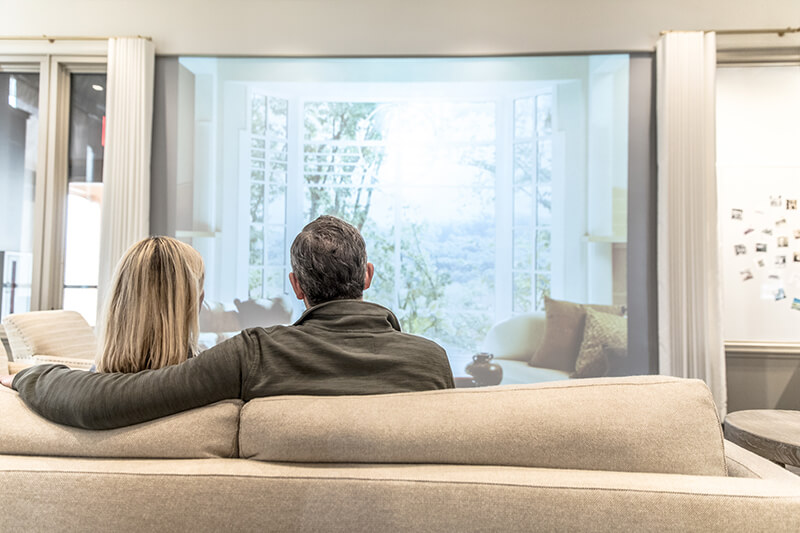 2 people on a couch looking through large Marvin Window