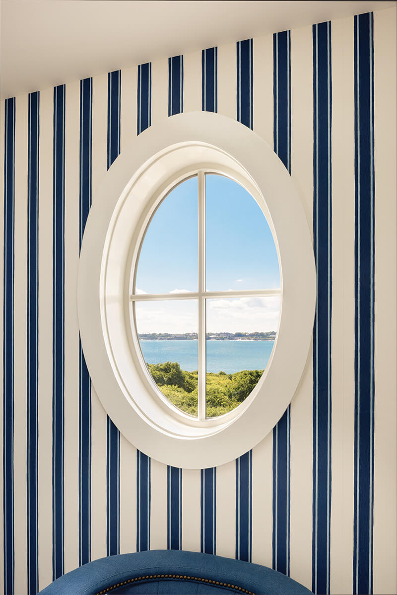 A porthole-inspired oval window with a view of the Atlantic ocean.