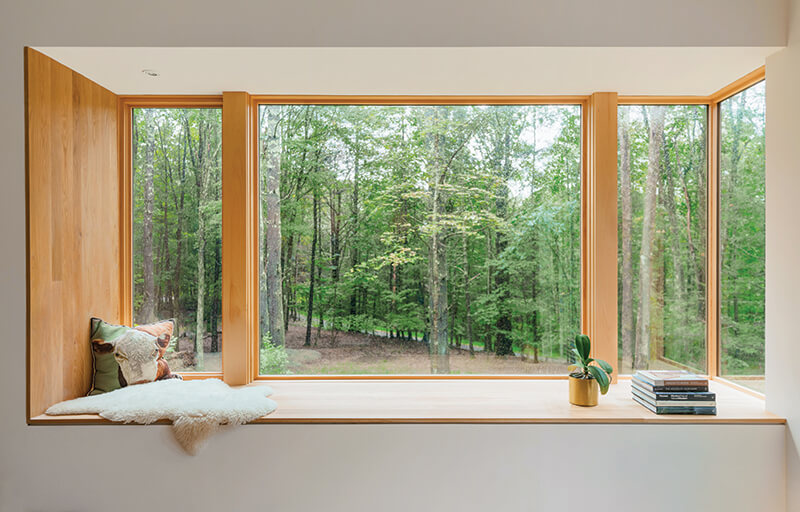 Picture windows and a corner window create a window seat that captures forest views.