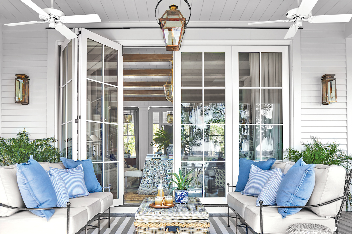 A porch featuring a Marvin Signature Ultimate Bi-Fold Door and resort style decor.