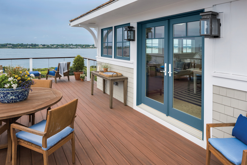 A resort style deck featuring Marvin Signature Ultimate Sliding French Doors and Ultimate casement windows.