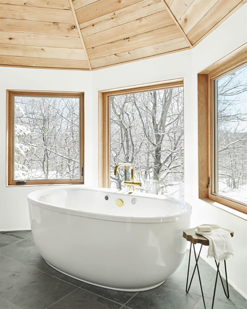 Traditional style bathtub in front of set of 3 Marvin Windows