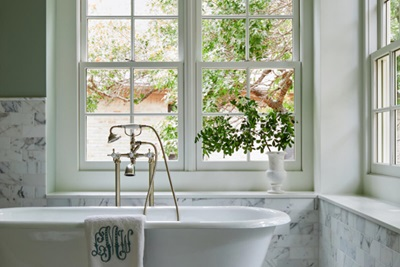 Close-up of traditional claw foot tub in front of Marvin Windows