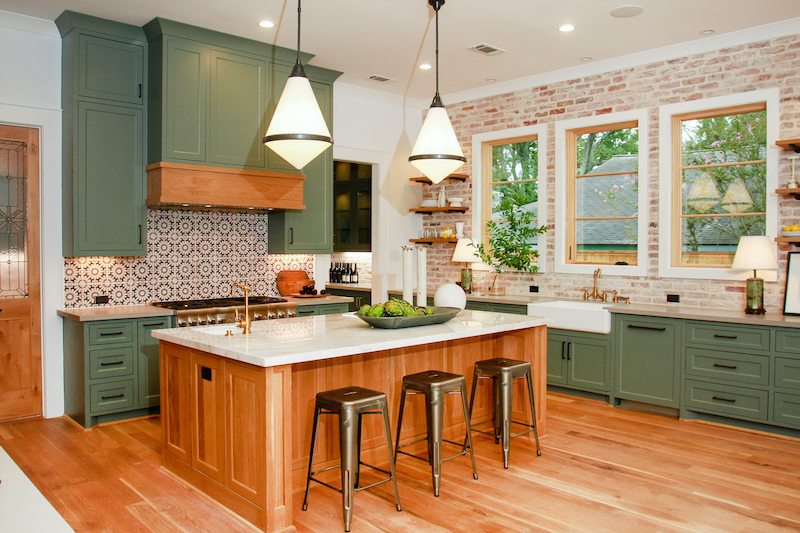 Modern farmhouse kitchen with sage green cupboards, exposed brick, and Marvin windows.