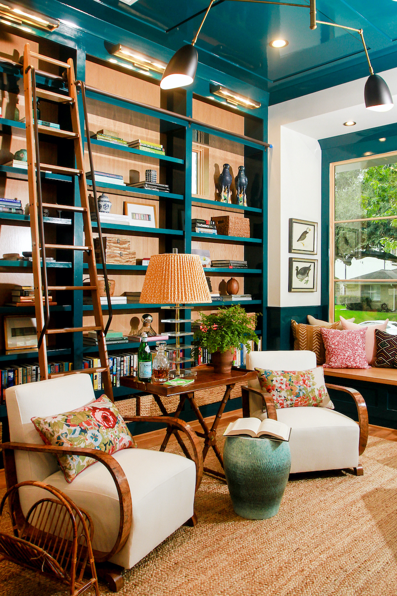 A library or reading room featuring blue built-ins and Marvin windows.