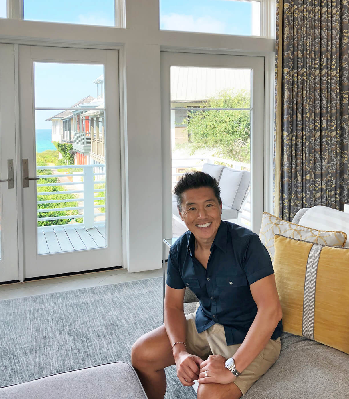 Vern Yip sitting on couch in front of large Marvin Windows at his beach home