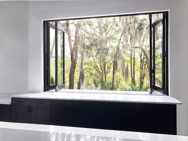 Marvin Bi-Fold Windows with a view of trees from inside a modern kitchen with white countertops and black cabinets.