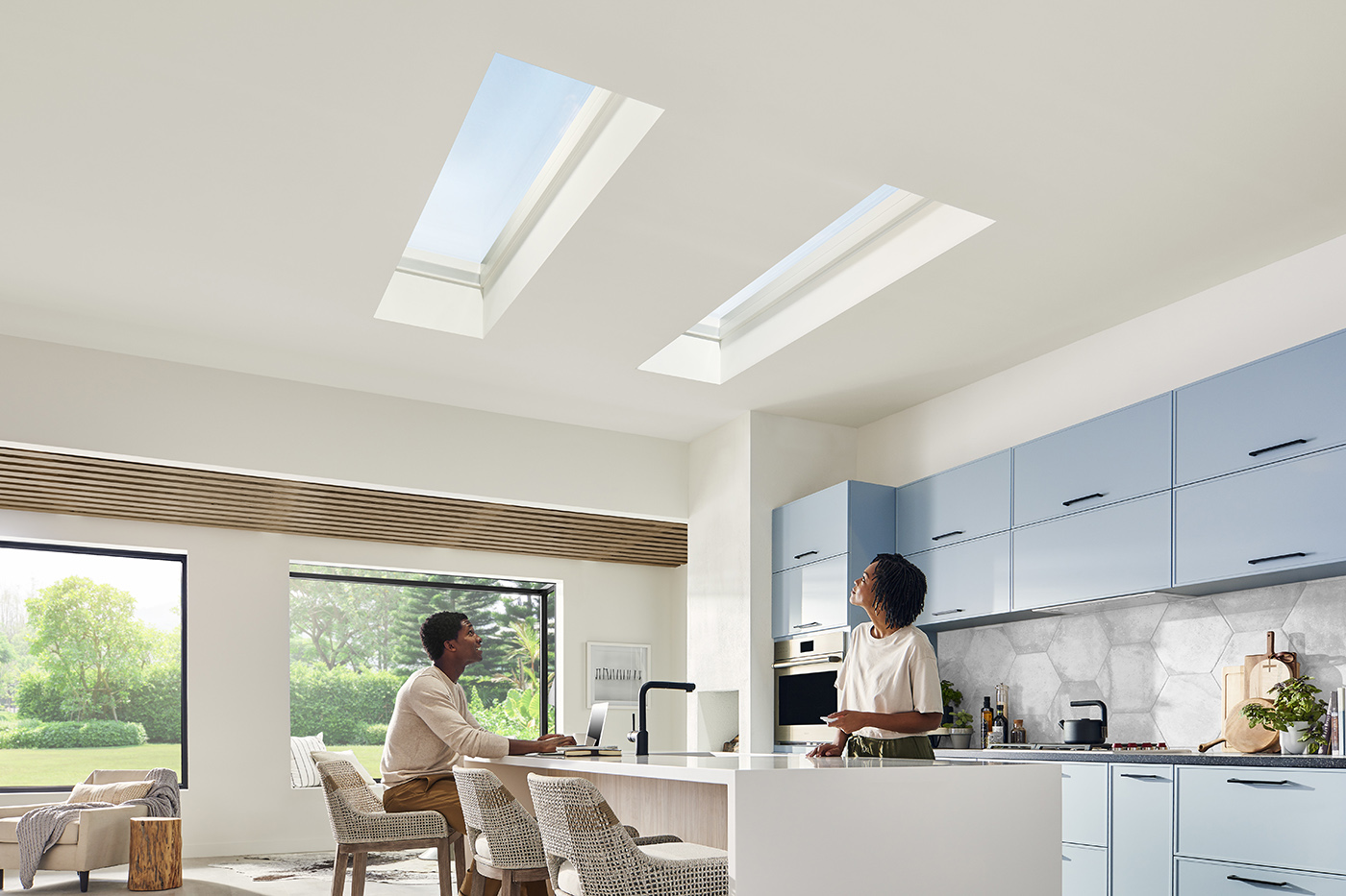 A man and woman in a modern kitchen featuring Marvin Awaken Skylights and Marvin Skycove.