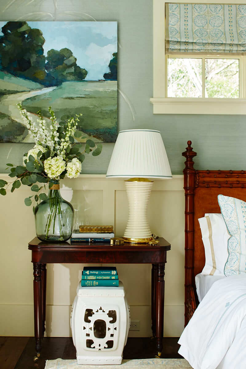 Nightstand with lamp and flowers next to bed