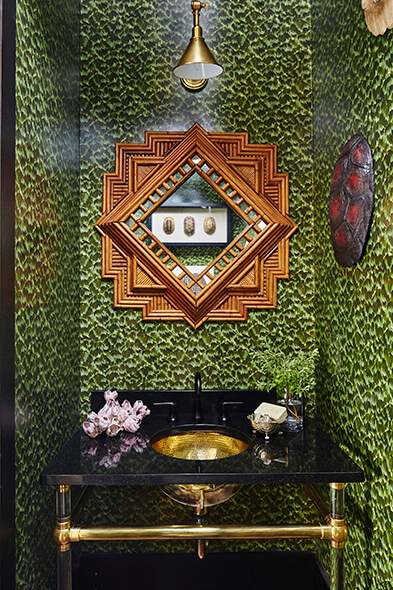 Unique bathroom with wallpaper and gold colored sink