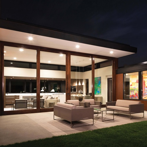 Exterior View At Night Of Patio And House With Signature Ultimate Lift And Slide Door