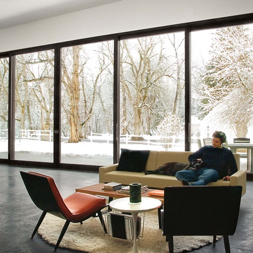 Man In Living Room With Snowy Scene Outside Through Signature Ultimate Lift And Slide Door