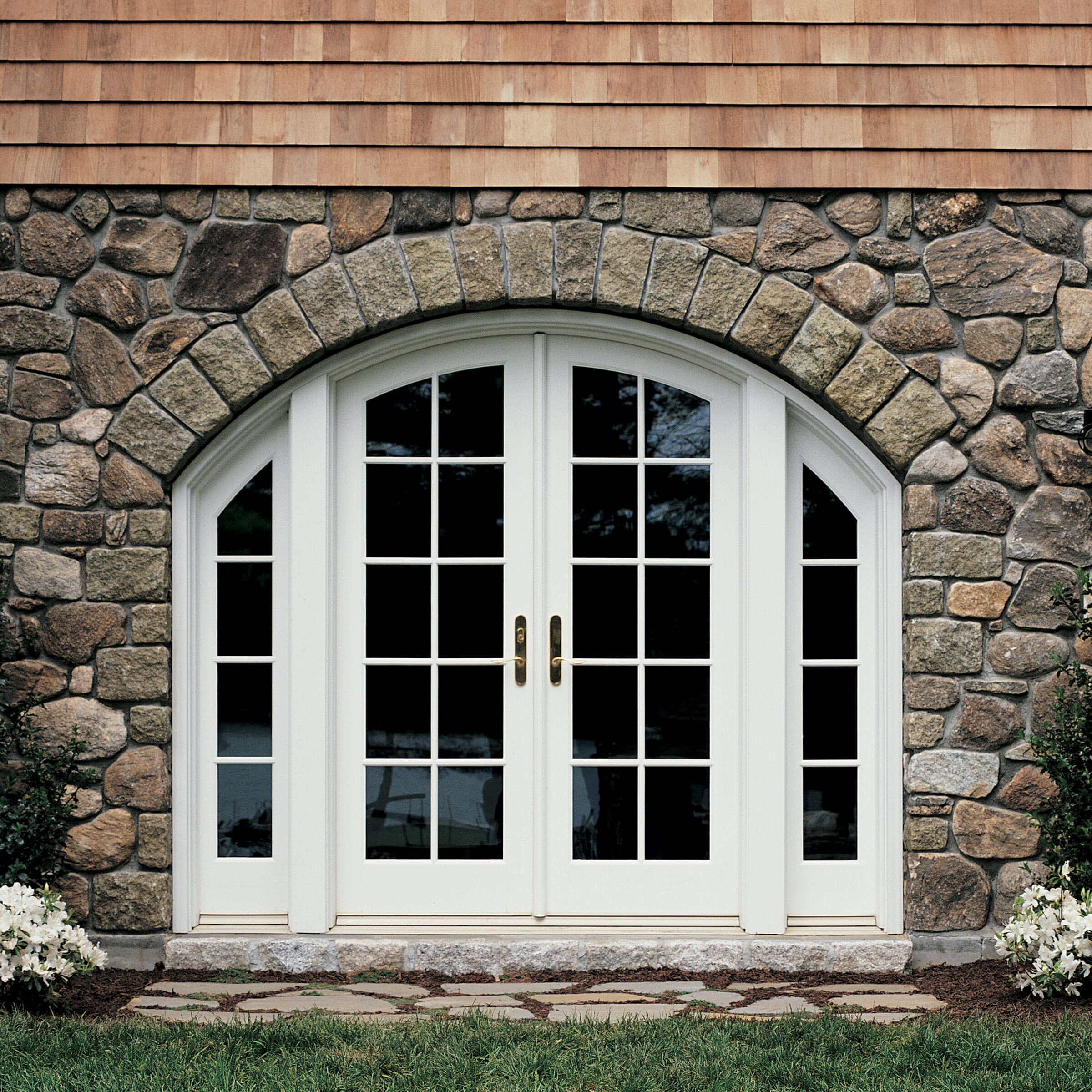 Stone-Faced Exterior View Of House With Signature Ultimate Swinging Arch Top French Door