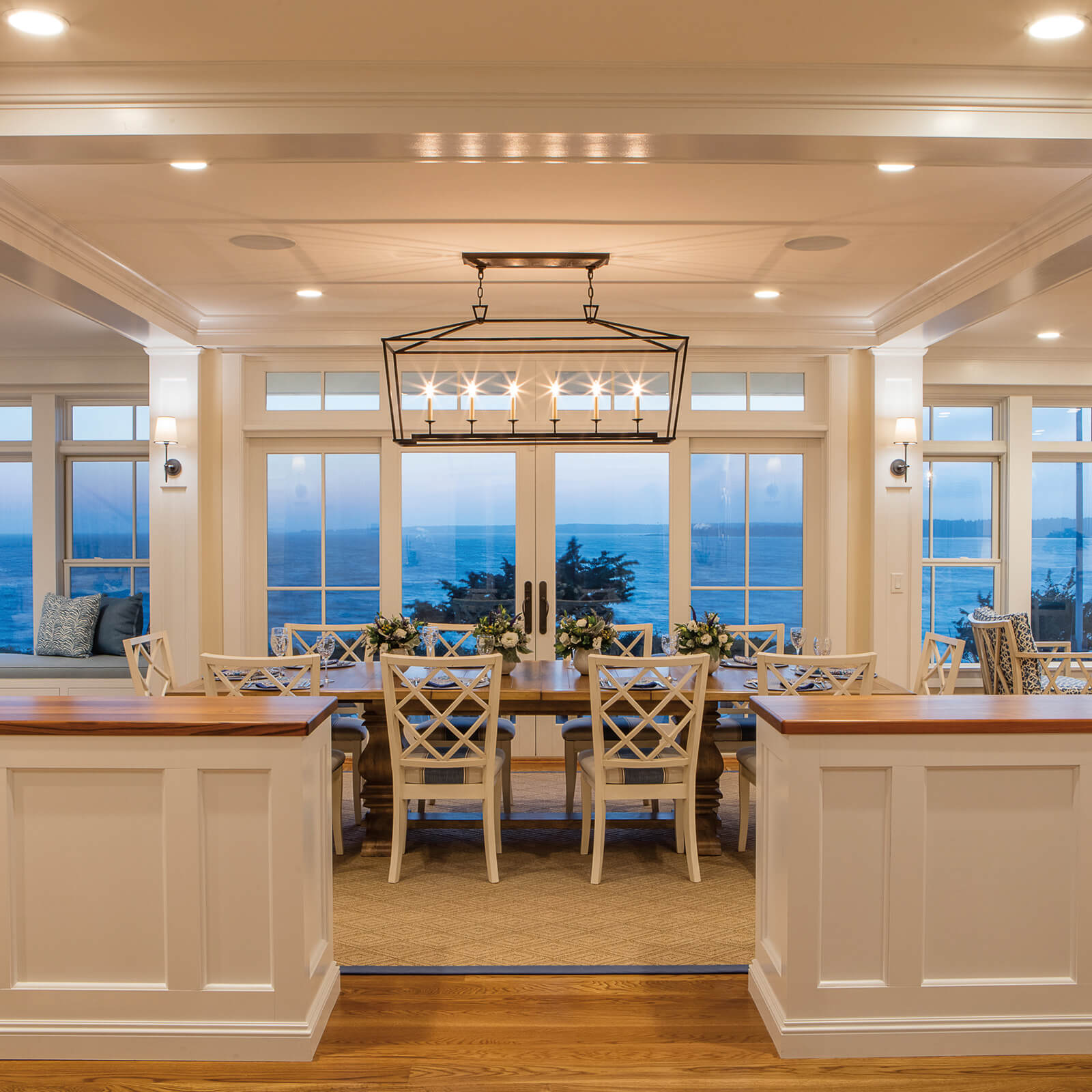 Kitchen and Dinning room with tray ceiling with a waterfront view through Marvin Elevate Sliding French Door and Double Hung Windows