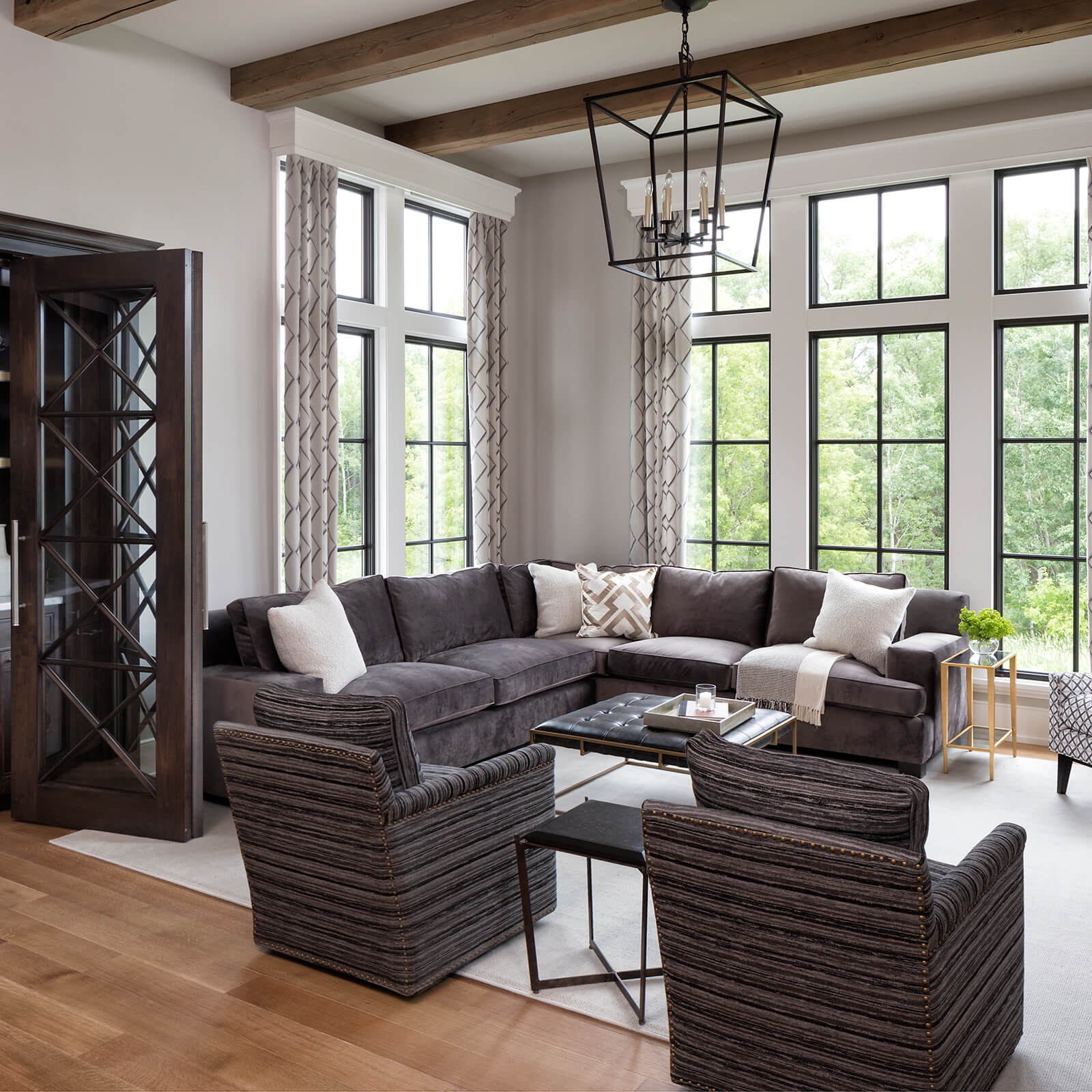 Large living area with tall ceilings and exposed beams with large Marvin Signature Ultimate Casement Windows