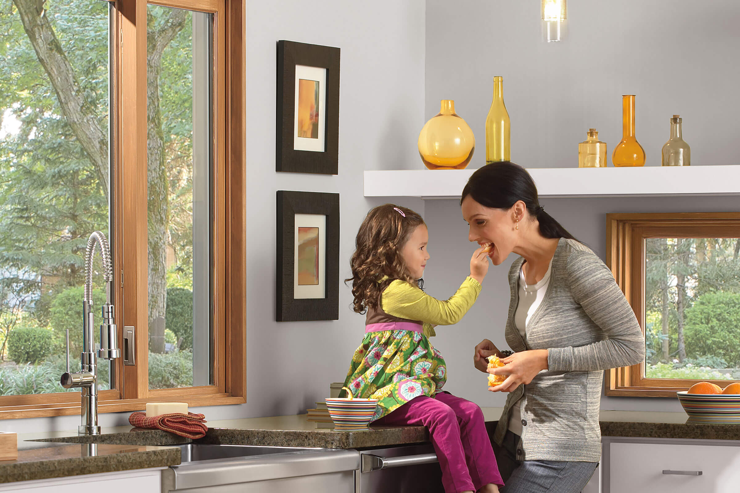 Mother And Daughter In Kitchen With Signature Ultimate Glider Window