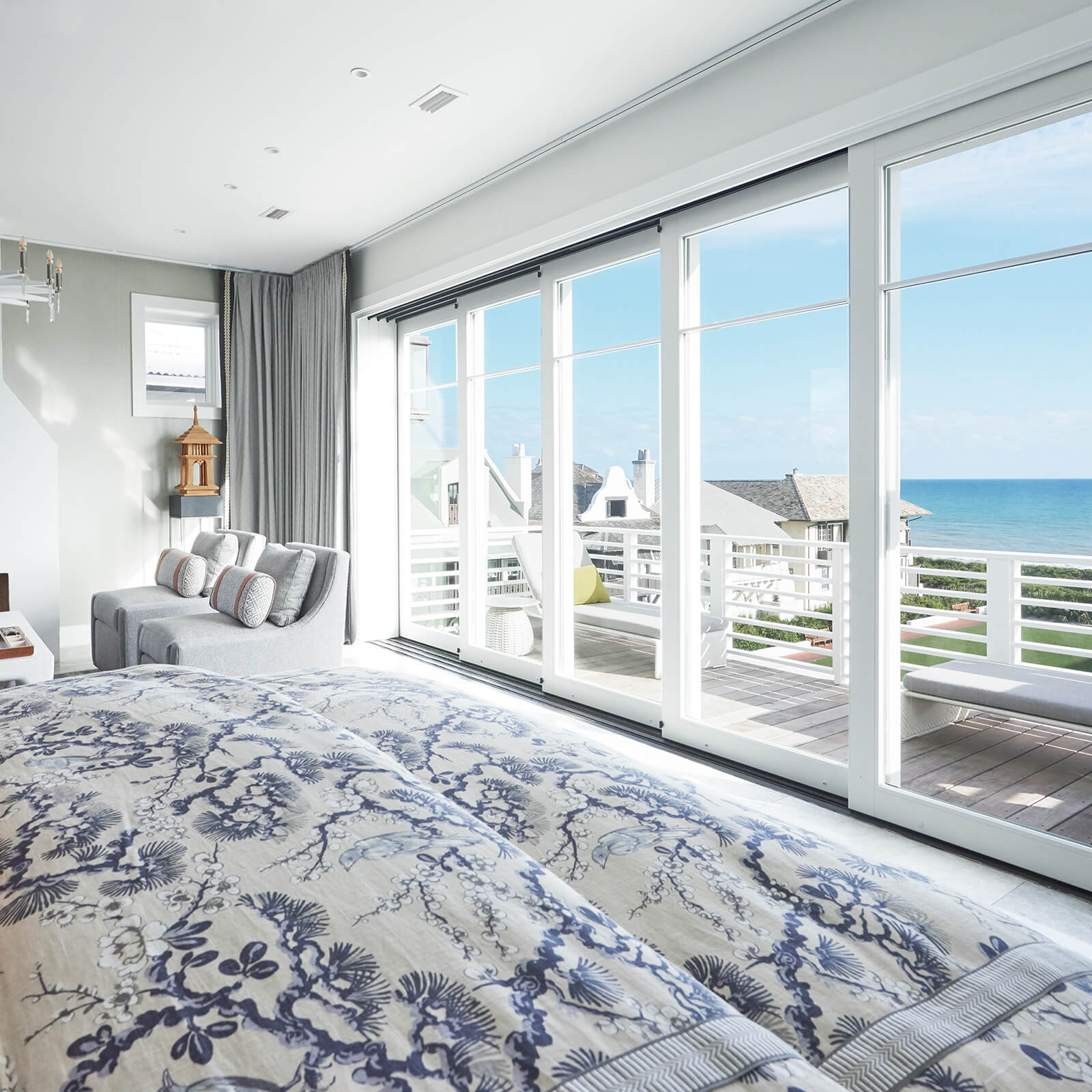 A bedroom with a deck and multi-slide doors overlooking the ocean in Vern Yip's Rosemary Beach home.