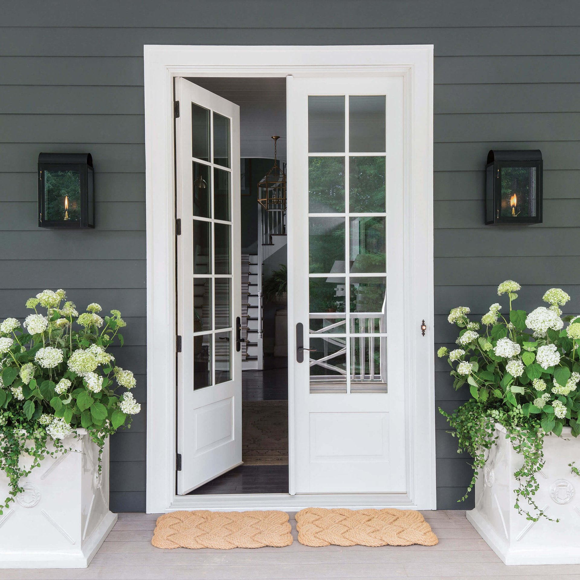 Exterior View Of House Entrance With An Open Signature Ultimate Swinging French Door